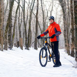 Mountain Biker with Bike on the Snowy Trail in Beautiful Winter Forest Royalty Free Stock Photography