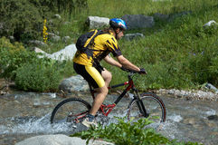 Mountain biker and creek Royalty Free Stock Images
