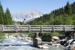 Mountain biker crossing bridge Stock Photography