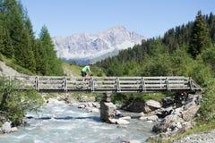 Mountain biker crossing bridge Royalty Free Stock Image