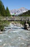Mountain biker crossing bridge Royalty Free Stock Photo