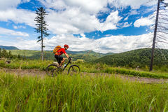 Mountain biker cycling riding in woods and mountains. Mountain biker riding on bike in summer inspirational mountains landscape. Man cycling MTB on enduro trail Stock Photos