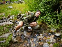 Mountain Biker drinking from a stream Royalty Free Stock Images