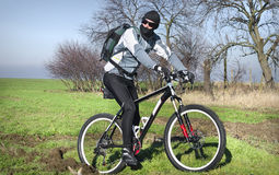 Mountain biker in field. Side view of mountain biker in wintry clothes riding over countryside field royalty free stock image