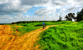 Mountain biker in field Royalty Free Stock Images