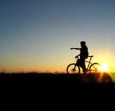 Mountain biker girl silhouette. In sunrise stock photography