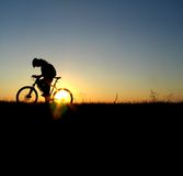 Mountain biker girl silhouette. In sunrise stock photos