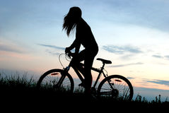 Mountain biker girl silhouette. In sunrise Royalty Free Stock Photography