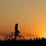 Mountain biker girl silhouette. In sunset Royalty Free Stock Photos