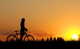 Mountain biker girl silhouette. In sunset Royalty Free Stock Photo