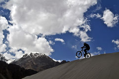 Mountain biker in Himalaya. Mountain biker doing a trick in the Nubra Valley, in Ladakh, Northern India Royalty Free Stock Photos