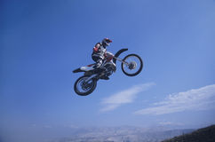 Mountain Biker Jumping Against Blue Sky Stock Photo