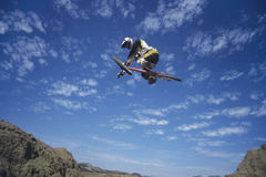Mountain Biker Jumping Against Blue Sky royalty free stock photos