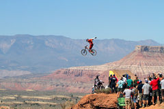 Mountain biker jumps cliff and crowd watches Stock Image