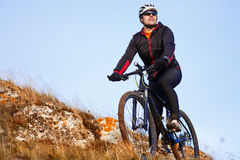 Mountain biker looking at inspiring mountain landscape, standing with bicycle. Royalty Free Stock Images
