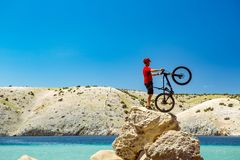 Mountain biker looking at mountains and beach Royalty Free Stock Photography