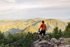 Mountain biker looking at view on bike trail in autumn mountains. Mountain biker looking at inspiring landscape on bike rocky trail in autumn mountains. Riding Royalty Free Stock Image