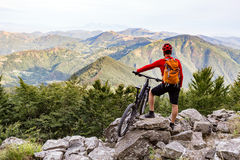 Mountain biker looking at view on bike trail in autumn mountains Royalty Free Stock Photography