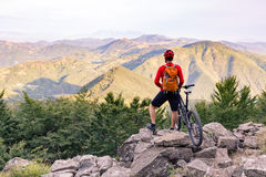 Mountain biker looking at view on bike trail in autumn mountains Royalty Free Stock Photo