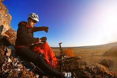 Mountain biker looking at view on bike trail in spring landscape. Male rider resting on cycling trip in nature. Sport fitness, motivation and inspiration in stock photography