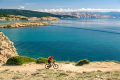 Mountain biker looking at view and riding a bike Royalty Free Stock Images