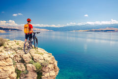 Mountain biker looking at view and riding a bike Royalty Free Stock Photos