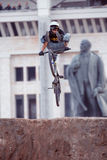 Mountain biker makes a heel clicker trick in front of Lenin monument Stock Photos