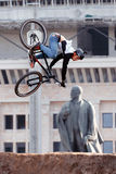 Mountain biker makes a stunt in front of Lenin monument Stock Images