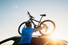 Mountain biker man takes of his bike from the car roof royalty free stock photography