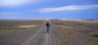 Mountain biker on old desert road Royalty Free Stock Photos