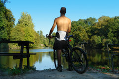 Mountain-biker overlooking pond. Stock Images