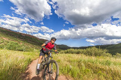 Mountain Biker in red jersey from low wide angle stock image