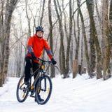 Mountain Biker Resting Bike on the Snowy Trail in Beautiful Winter Forest Stock Photo