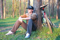 Mountain biker resting in forest Stock Photos