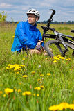 Mountain biker resting in a grass Royalty Free Stock Image