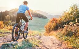 Mountain biker ride down from hill. Active and sport leisure con royalty free stock image