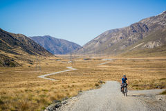 Mountain biker riding off road in valley Stock Photo