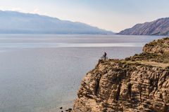 Mountain biker riding bike on rocks at the ocean Stock Images