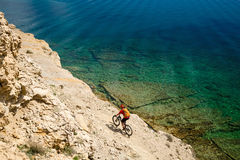 Mountain biker riding a bike on rocky trail path at sea Royalty Free Stock Photo