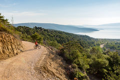 Mountain biker riding on bike at the sea Stock Images