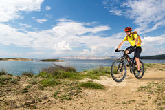 Mountain biker riding on bike at the sea and summer mountains. Man rider cycling MTB on country road or single track. Sport fitness motivation, inspiration in stock images
