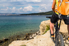 Mountain biker riding on bike at the sea and summer mountains Royalty Free Stock Image