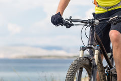 Mountain biker riding on bike at the sea and summer mountains. Stock Images