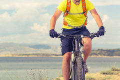Mountain biker riding on bike at the sea. And summer mountains. Man rider cycling MTB on country road or single track. Sport fitness motivation, inspiration in Royalty Free Stock Photo