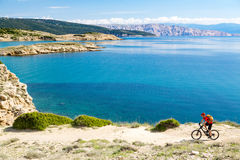Mountain biker riding on bike at seaside path Royalty Free Stock Photos
