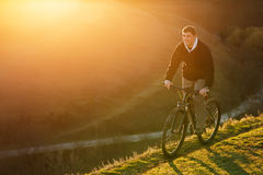 Mountain biker riding on bike in spring inspirational mountains landscape. inspiration outdoors in sunset. Mountain biker riding on bike in spring inspirational royalty free stock images
