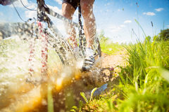 Mountain Biker Riding Through A Dirty Puddle Stock Photo