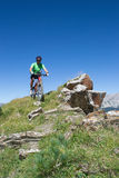 Mountain biker riding downhill in Swiss Alps Stock Images