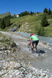 Mountain biker riding through stream Royalty Free Stock Image