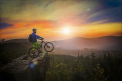 Mountain biker riding at sunset on bike in summer mountains fore. St landscape. Man cycling MTB flow trail track. Outdoor sport activity Stock Images
